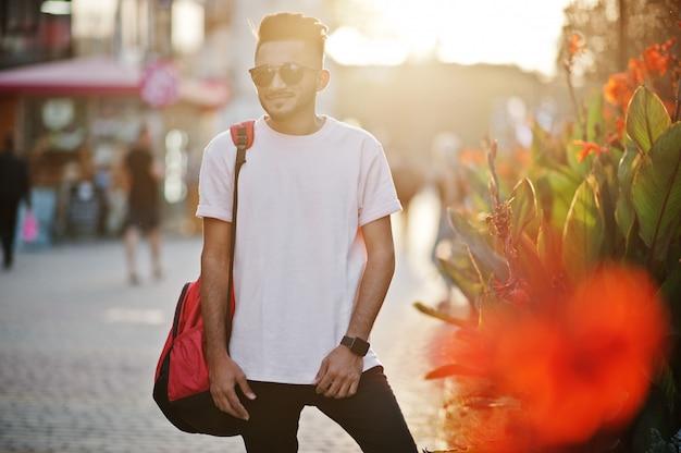 Stylowy Broda W Różowym T-shircie, Okularach Przeciwsłonecznych I Plecaku Modelu Indii Pozował Na Ulicy Przy Zachodzie Słońca Premium Zdjęcia