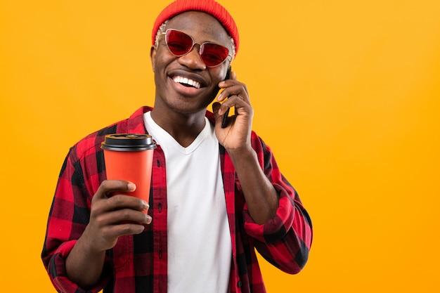 Stylowy Czarny Amerykanin W Kraciastej Czerwonej Koszuli Ze Szklanką Kawy Na żółto Premium Zdjęcia