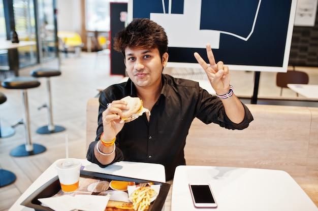 Stylowy Indyjski Mężczyzna Siedzący W Kawiarni Fast Food I Jedzenie Hamburgera I Gest Dłoni Znak Pokoju. Premium Zdjęcia