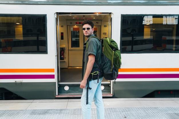 Stylowy męski turysta w okularach i plecak stojący przed pociągiem Darmowe Zdjęcia