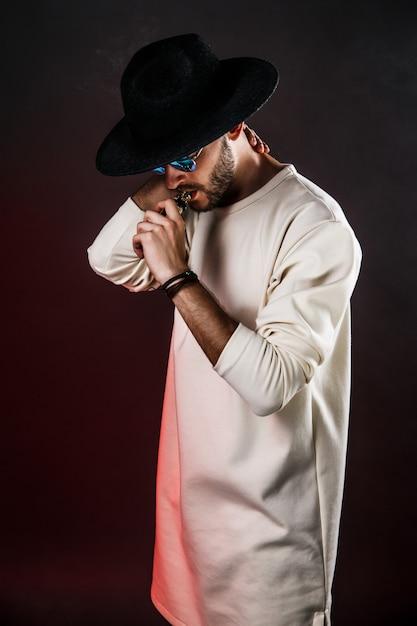 Stylowy mężczyzna w kapeluszu vaping Premium Zdjęcia