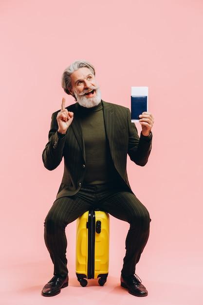Stylowy Mężczyzna W średnim Wieku W Garniturze Siedzi Na żółtej Walizce I Ma Paszport. Premium Zdjęcia