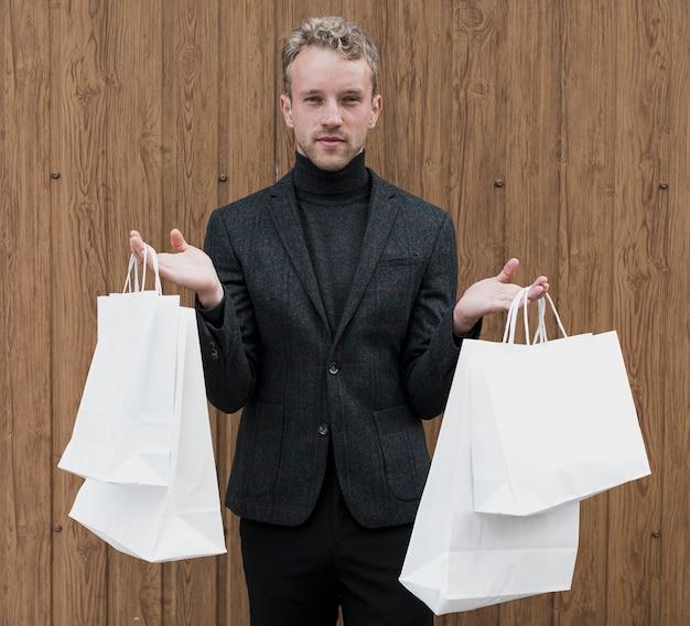 Stylowy mężczyzna z torby na zakupy w obu rękach Darmowe Zdjęcia