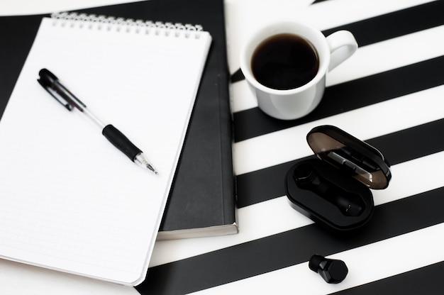Stylowy minimalistyczny obszar roboczy z makiety notesem, ołówkiem, filiżanką kawy, słuchawką bezprzewodową Premium Zdjęcia