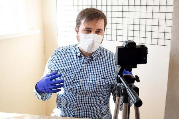 Sukces Człowieka Nagrywanie Wideo, Przy Użyciu Aparatu Cyfrowego W Biurze Lub W Domu, Koronawirus, Choroba, Infekcja, Kwarantanna, Maska Medyczna Premium Zdjęcia