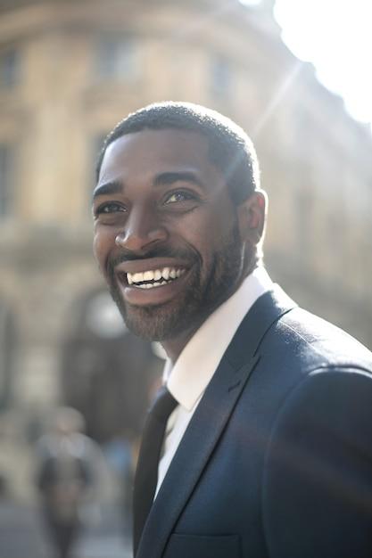 Sukcesy biznesmen uśmiechając się dużo podczas spaceru na ulicy Premium Zdjęcia