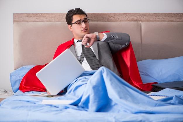 Super bohatera bizneswoman pracuje w łóżku Premium Zdjęcia