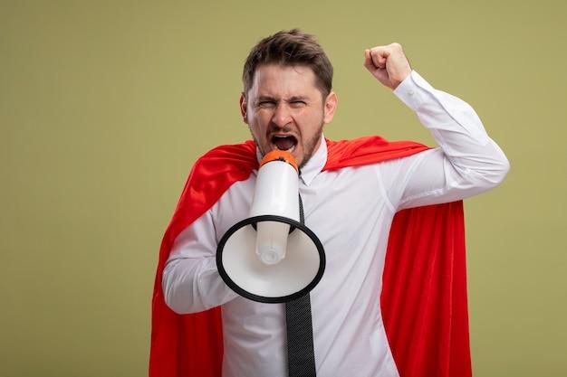 Superbohater Biznesmen W Czerwonej Pelerynie Krzyczy Do Megafonu Z Agresywnym Wyrazem Podnosząc Pięść Stojącą Nad Zieloną ścianą Darmowe Zdjęcia