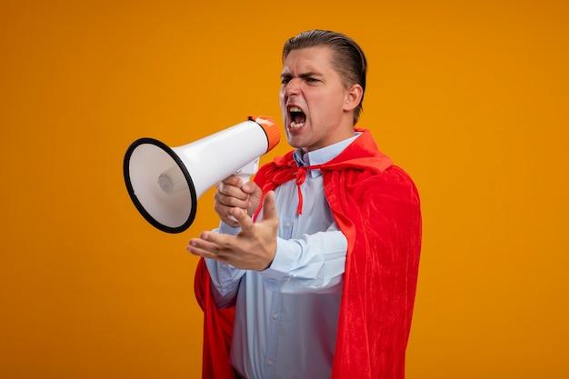 Superbohater Biznesmen W Czerwonej Pelerynie Krzyczy Do Megafonu Z Agresywnym Wyrazem Ręki Stojącej Nad Pomarańczową ścianą Darmowe Zdjęcia