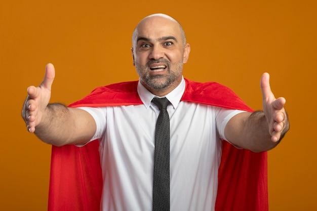 Superbohater Biznesmen W Czerwonej Pelerynie Patrząc Na Przód Uśmiechnięty Przyjazny Gest Powitalny Z Rękami Stojącymi Na Pomarańczowej ścianie Darmowe Zdjęcia