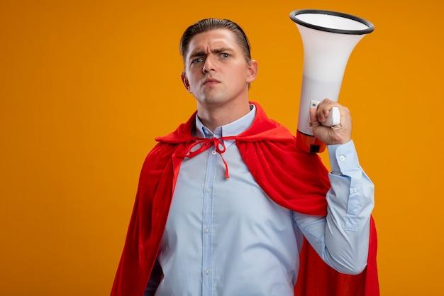 Superbohater Biznesmen W Czerwonej Pelerynie Trzymając Megafon Z Poważną Zmarszczoną Twarzą Stojącą Nad Pomarańczową ścianą Darmowe Zdjęcia
