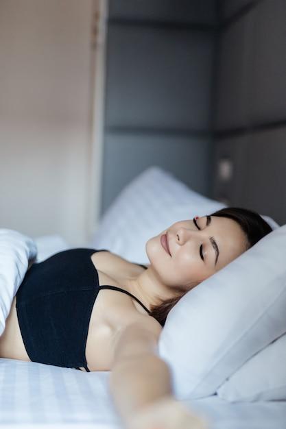 Superseksualna Młoda Kobieta, Leżąc W łóżku I Rozciągnij Ramiona Darmowe Zdjęcia