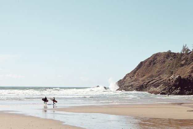 Surfers In The Distance Na Kamienistej Plaży Darmowe Zdjęcia