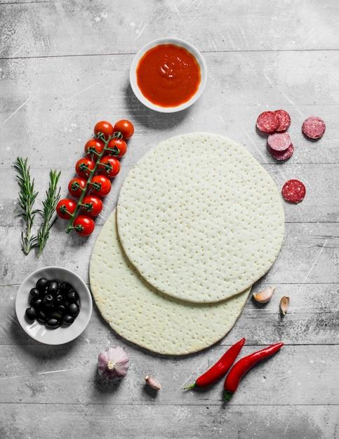 Surowa Pizza. Rozwałkować Okrągłe Ciasto Z Oliwkami, Kiełbasą I Pomidorami Na Białym Drewnianym Stole Premium Zdjęcia
