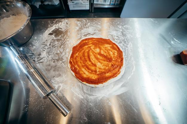 Surowe Ciasto Do Przygotowania Pizzy Ze Składnikiem: Sos Pomidorowy, Mozzarella, Pomidory, Premium Zdjęcia