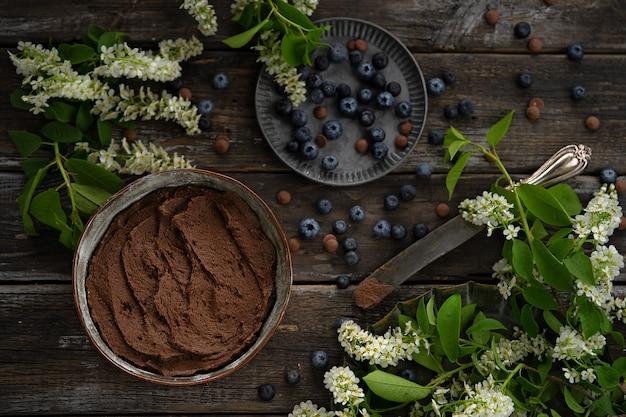Surowe ciasto w foremce z miedzi. jagody jagodowe i kwiaty wiśni Premium Zdjęcia