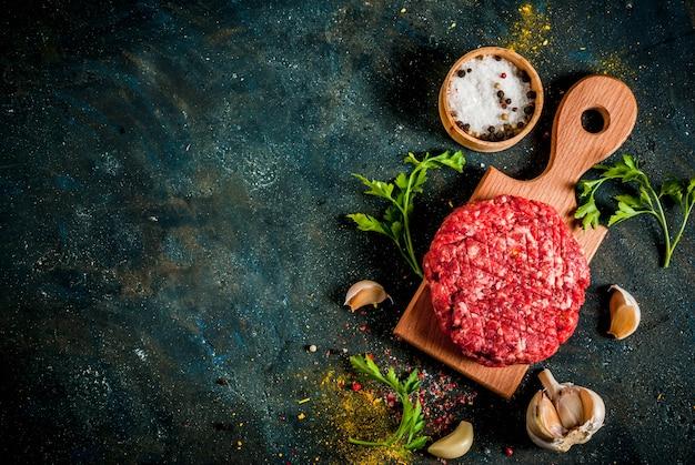 Surowe Kotlety Burgerowe Z Solą, Pieprzem, Olejem, Ziołami I Przyprawami Premium Zdjęcia