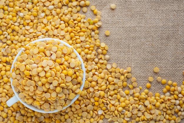 Surowe nasiona soi w białej szklance umieszczonej na podłodze. Darmowe Zdjęcia
