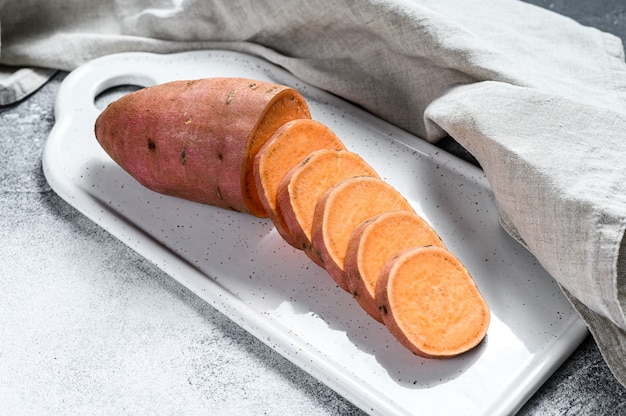Surowe Słodkie Ziemniaki Na Desce Do Krojenia, Ignam Organiczny. Warzywa Rolne Szare Tło Premium Zdjęcia