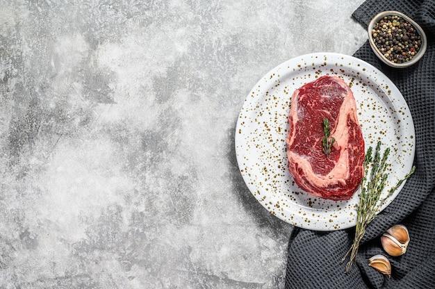 Surowe świeże Mięso Stek Ribeye Z Przyprawami Na Desce Do Krojenia Premium Zdjęcia