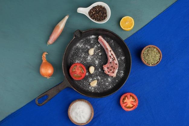 Surowe żeberka Na Czarnej Patelni Z Warzywami I Przyprawami Na Niebieskim Stole. Darmowe Zdjęcia