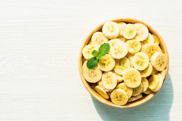 Surowi żółci bananów plasterki w drewnianym pucharze Darmowe Zdjęcia