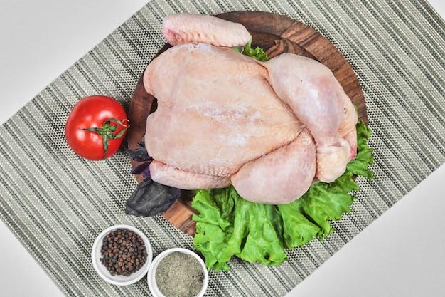 Surowy Cały Kurczak Na Drewnianym Talerzu Z Sałatą, Pomidorem I Przyprawami Darmowe Zdjęcia