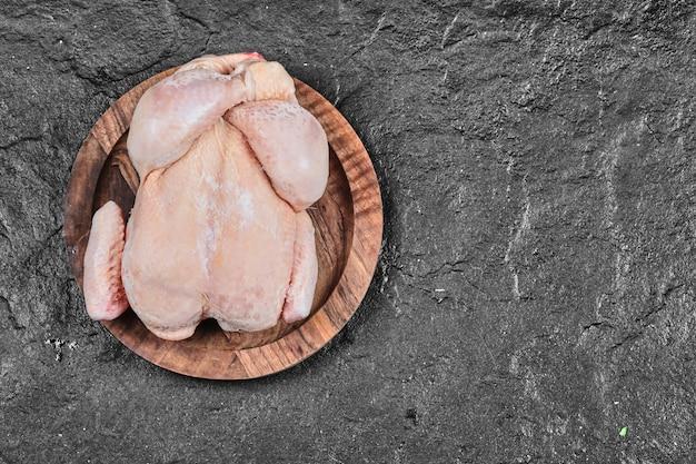 Surowy Cały Kurczak Na Talerzu Ceramicznym Samodzielnie Na Białej Powierzchni Darmowe Zdjęcia