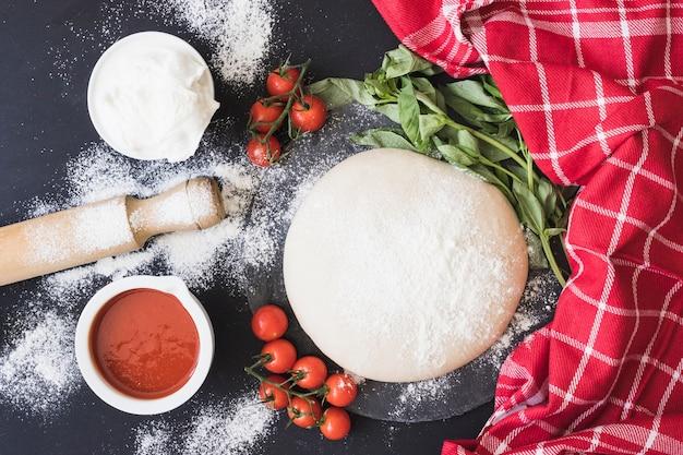 Surowy ciasto dla pizzy z składnikami na kuchennym kontuarze Darmowe Zdjęcia