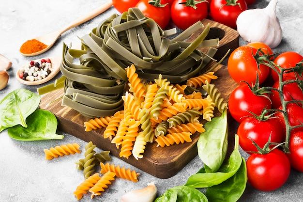 Surowy makaron tagliatelle ze szpinakiem i makaronem fusilli ze szpinakiem i pomidorami Premium Zdjęcia