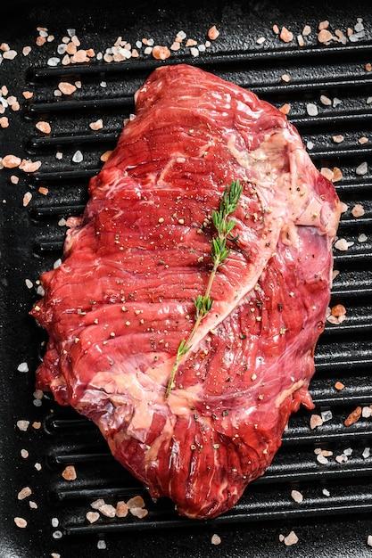 Surowy Marmurkowy Stek Wołowy Na Patelni Grillowej Premium Zdjęcia