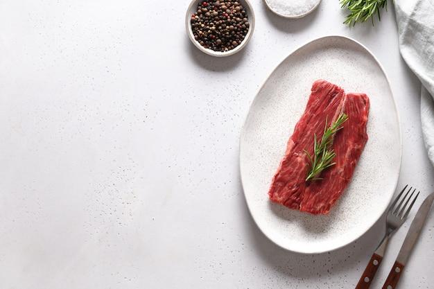 Surowy Stek Ribeye Z Rozmarynem Na Białym Tle. Skopiuj Miejsce Premium Zdjęcia