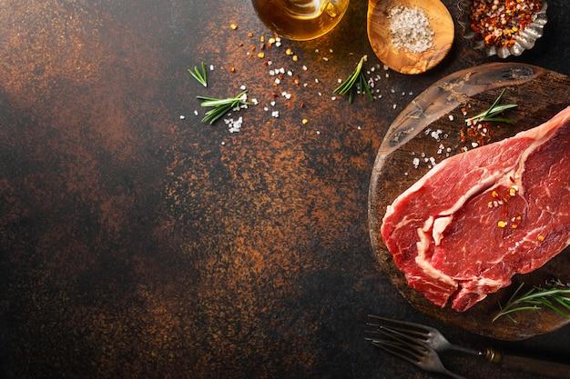 Surowy wołowina stek z składnikami na stole Premium Zdjęcia