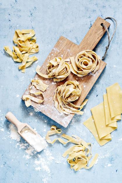 Surowy żółty Włoski Makaronu Pappardelle, Fettuccine Lub Tagliatelle, Zamyka Up. Gotowanie Jajecznego Makaronu Domowej Roboty, Makaron Z Długim Walcem, Niegotowane Spaghetti. Premium Zdjęcia