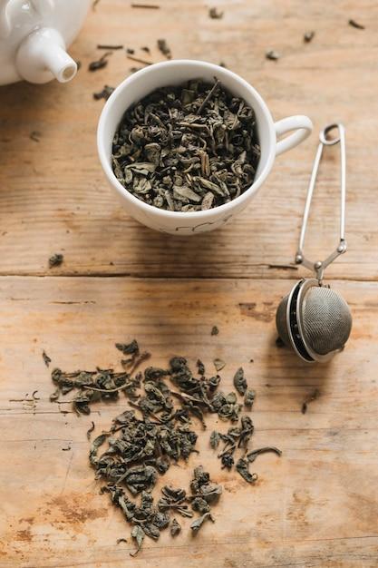 Susi herbaciani liście w filiżance z herbacianym durszlakiem na stole Darmowe Zdjęcia