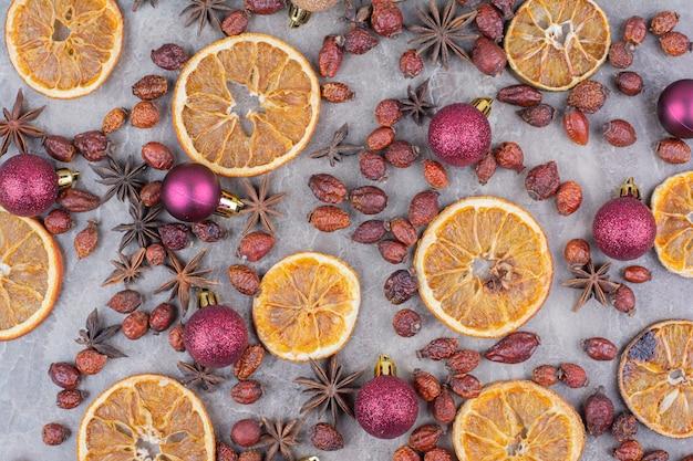 Suszona Pomarańcza Z Bombkami I Owocami Dzikiej Róży Na Kamiennej Powierzchni. Darmowe Zdjęcia