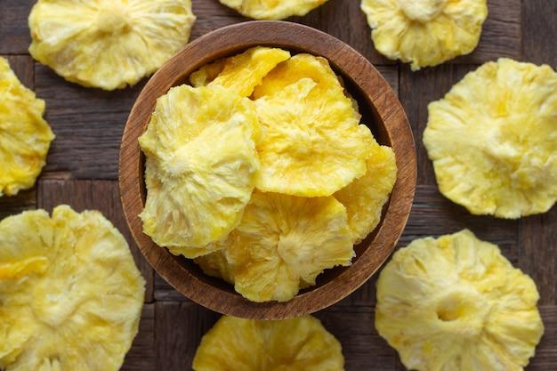 Suszone Owoce, Pierścienie Ananasa W Drewnianej Misce, Widok Z Góry. Premium Zdjęcia