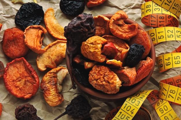 Suszone Owoce W Misce I Taśma Miernicza. Koncepcja Suszonych Owoców Na Szczupłe Ciało. Premium Zdjęcia