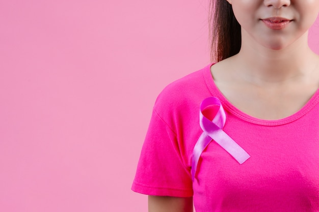 Świadomość raka piersi, kobieta w różowej koszulce z satynową różową wstążką na piersi, wspierająca świadomość raka piersi Darmowe Zdjęcia