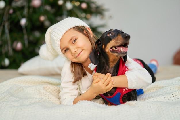 Świąteczna Bajka Magiczna. Mała Dziewczynka śmieje Się Ze Swoim Przyjacielem Jamnikiem, Niedaleko Drzewa Premium Zdjęcia