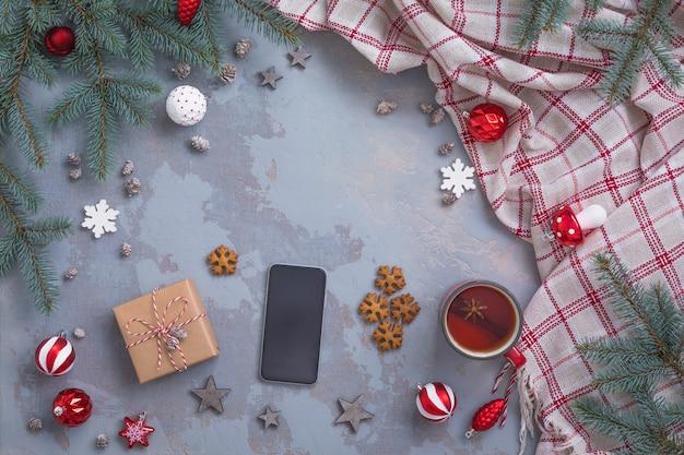 Świąteczna filiżanka do herbaty z cynamonem, ciastkami, gałązkami jodły, zabawkami, prezentami, smartfonem, kratą Premium Zdjęcia