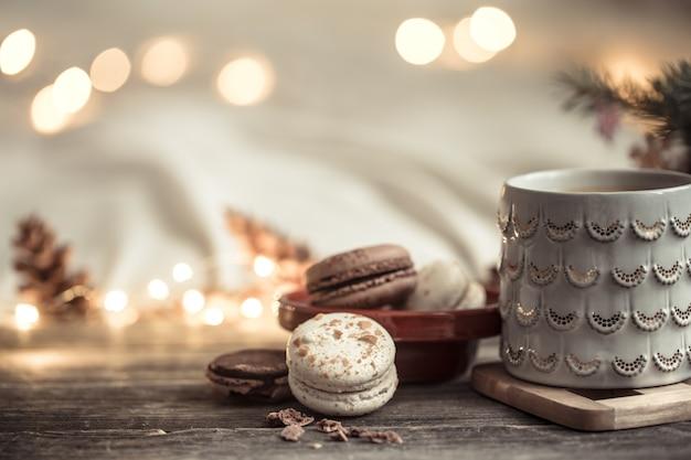 Świąteczna Filiżanka I Deser Z Makaronika Na Drewnie Ze światłami I świątecznym Wystrojem. Przytulność I Wygoda W Domu Premium Zdjęcia