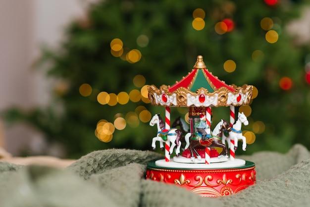 Świąteczna Muzyczna Karuzela Zabawkowa Na Tle Płonących świateł Choinki. Premium Zdjęcia