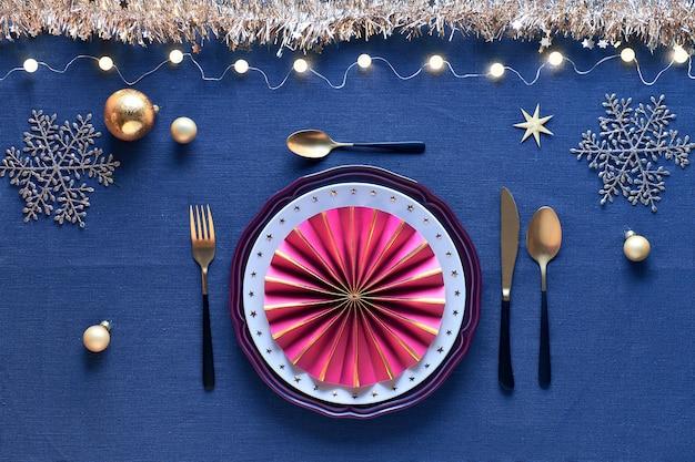 Świąteczna Oprawa Stołu W Kolorze Białym, Złotym, Bordowym Z Czarno-złotymi Sztućcami, Na Granatowym Lnianym Obrusie Premium Zdjęcia
