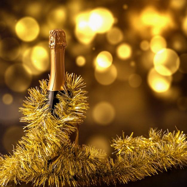 Świąteczna scena bożonarodzeniowa z butelką szampana i lśniącymi kofeinami. Premium Zdjęcia