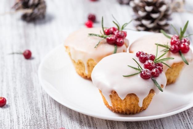Świąteczne babeczki z polewą cukrową, żurawiną i rozmarynem Premium Zdjęcia