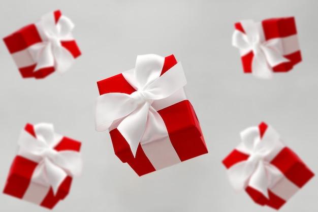 Świąteczne czerwone pudełka z białymi lewami lewituje na białym tle na szarym tle Premium Zdjęcia