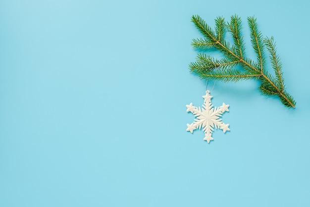 Świąteczne Dekoracje śnieżynka Zabawka Na Gałęzi Jodły Na Niebieskim Tle. Koncepcja Wesołych świąt Lub Szczęśliwego Nowego Roku. Premium Zdjęcia