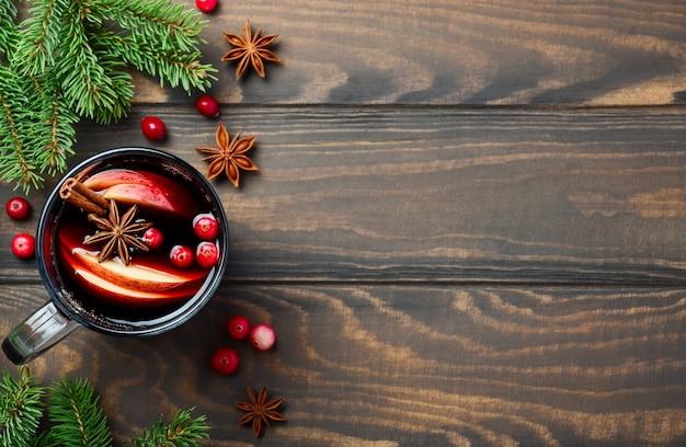 Świąteczne grzane wino z jabłkiem i żurawiną. koncepcja wakacje ozdobiona gałązkami jodły, żurawiną i przyprawami. Premium Zdjęcia