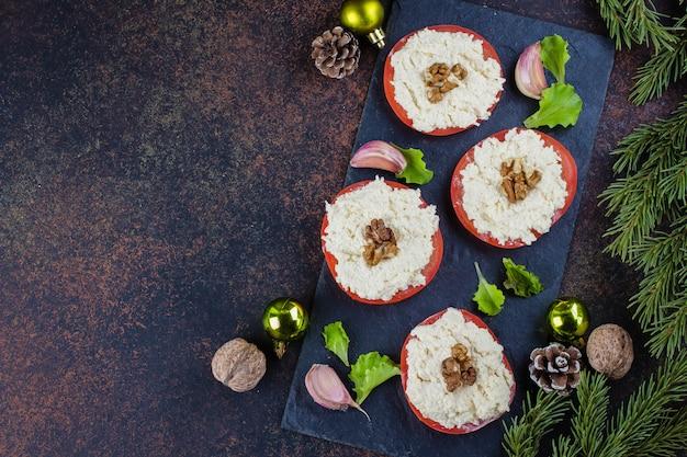 Świąteczne nakrycie stołu. pyszny pomidor przekąski z tartym serem z czosnkiem na ciemnym kamiennym stole. widok z góry, kopia przestrzeń. dekoracja świąteczna, oddział jodła Premium Zdjęcia